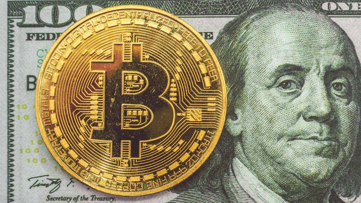 A bitcoin over a closeup of a 100 dollar bill