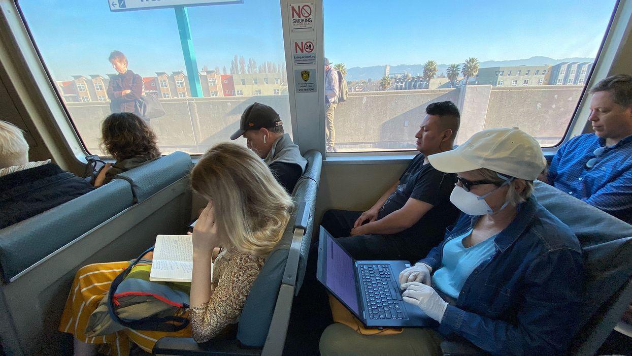 A commuter wearing a mask on a BART train in Oakland