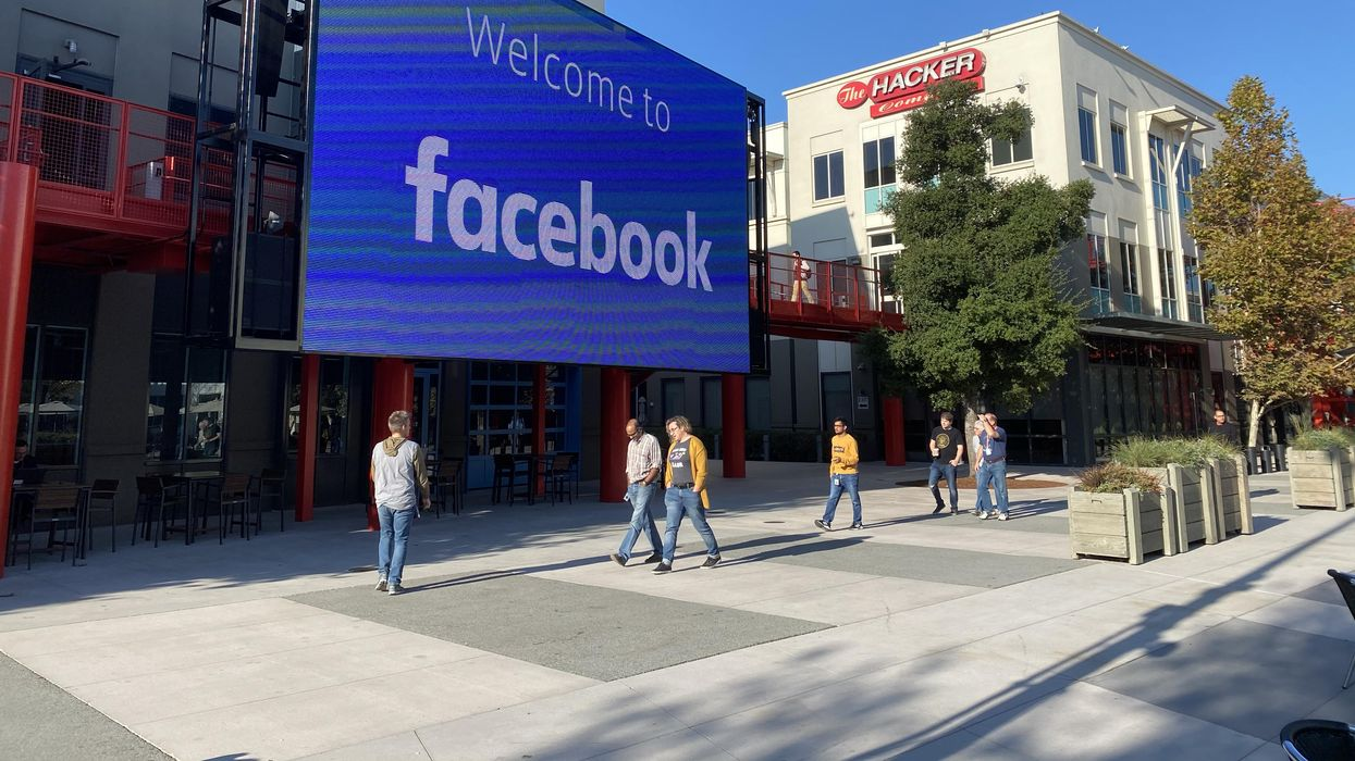 """A digital billboard reading """"Welcome to Facebook"""" displayed above a wide sidewalk with several pedestrians walking down it."""