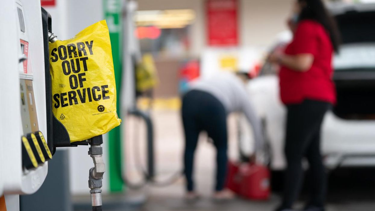 """A gas station pump that has a yellow sign on it that says """"sorry out of service"""""""