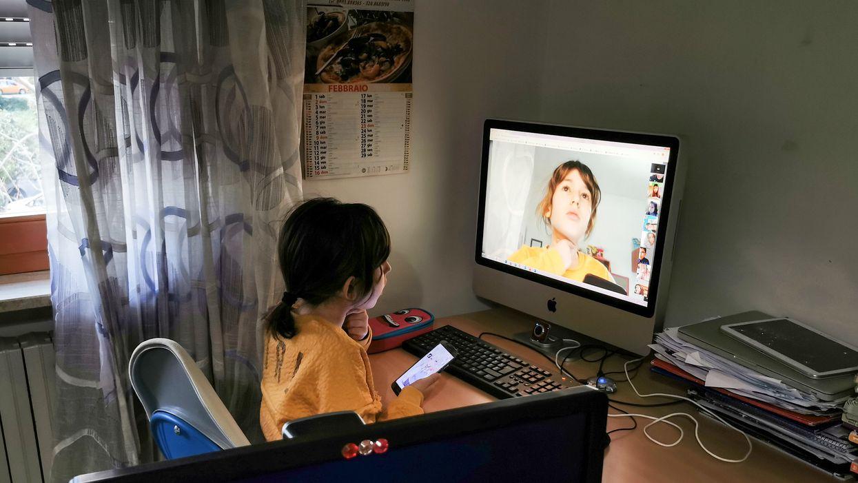 A girl sits at a computer