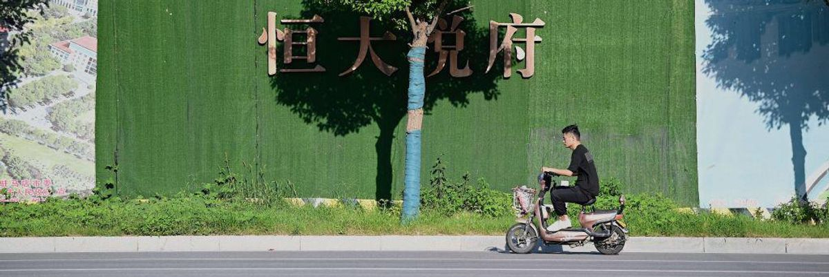 A man rides a bike in front of a tree and Evergrande's logo