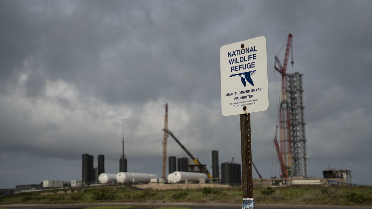 """A sign that reads """"National Wildlife Refuge"""" in front of the SpaceX launch site in Texas."""