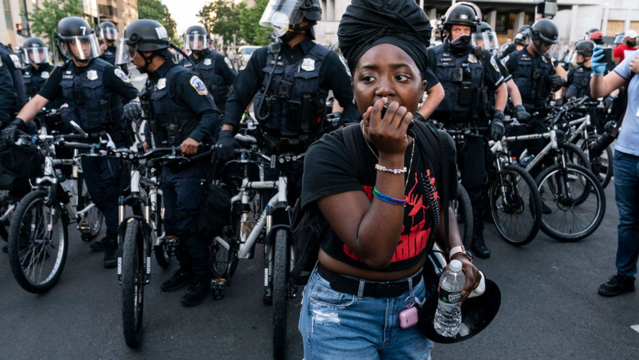 A woman stands in front of police during a protest
