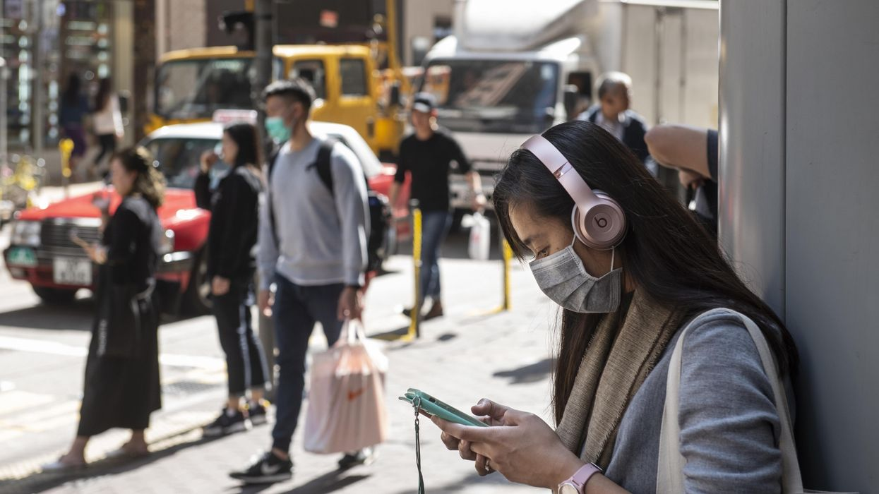 A woman in mask looks at phone