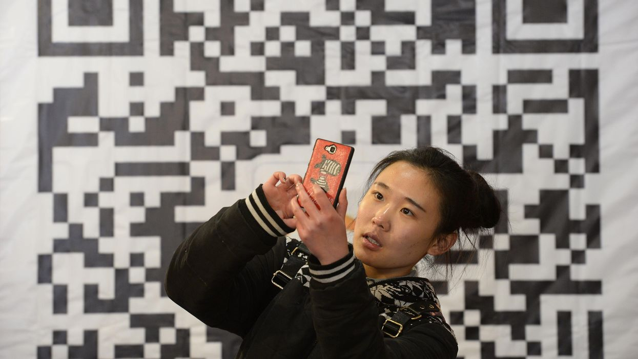 A woman stands in front of a large QR code.