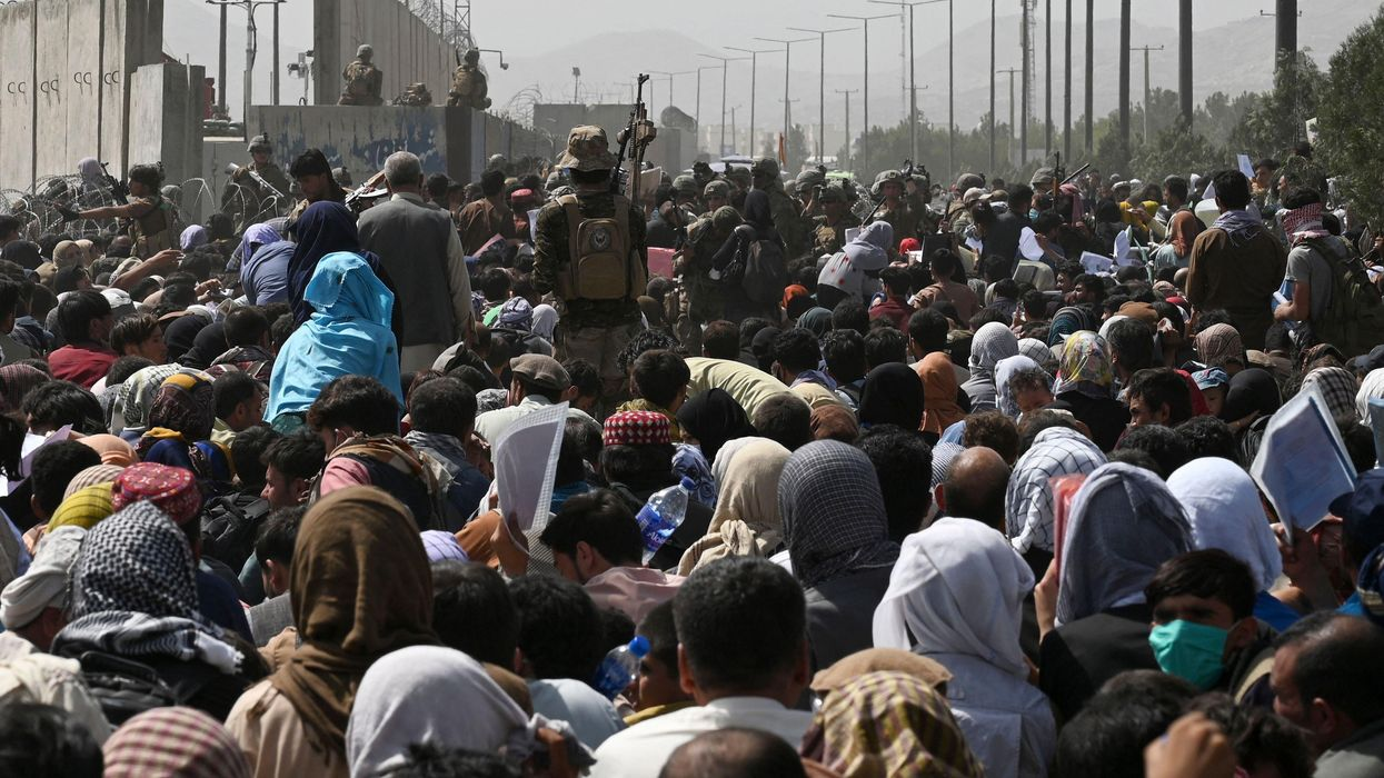 A large growd of people facing away from the camera, heading toward high cement walls with barbed whire on them.