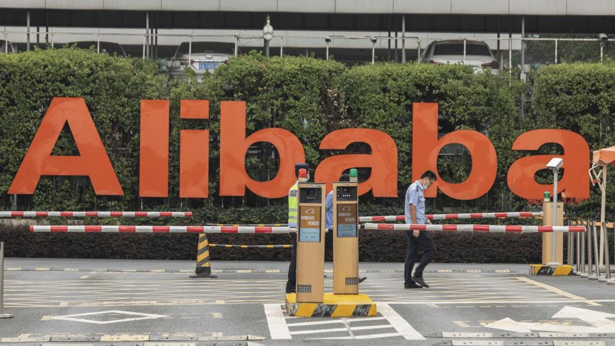 Two men pictured in an Alibaba company parking lot