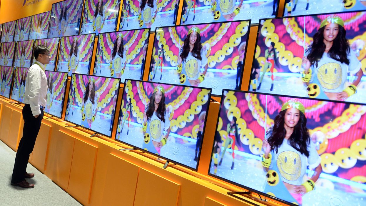 A man stands in front of televisions