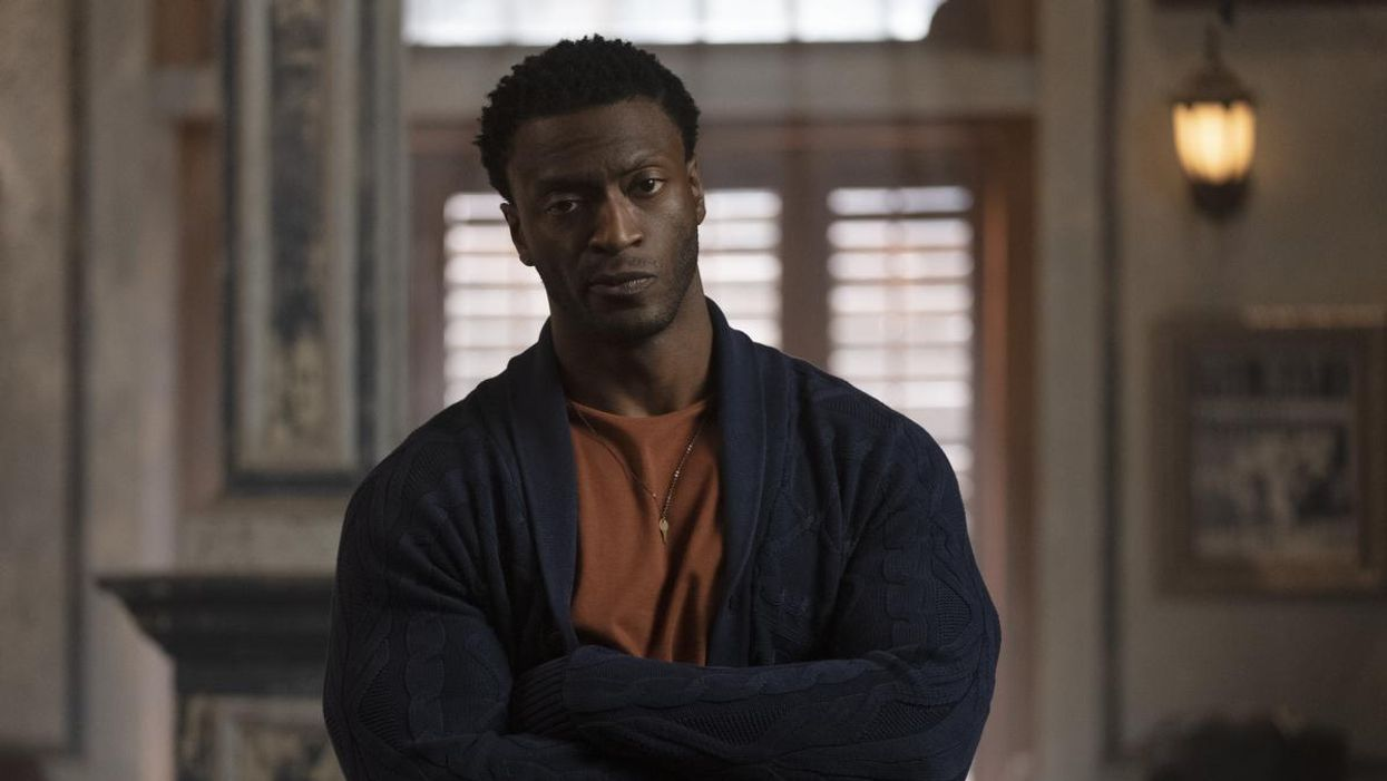 Actor Aldis Hodge looking at the camera with his arms folded