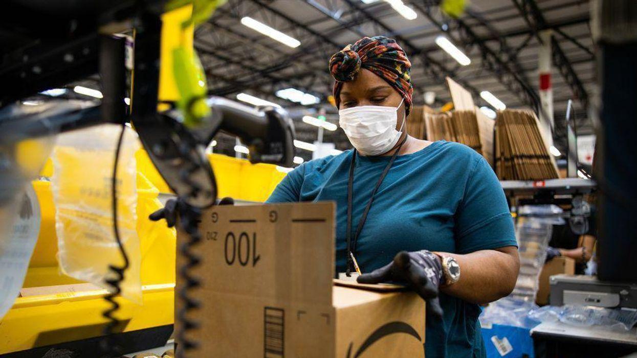An Amazon warehouse worker assembling a shipping box