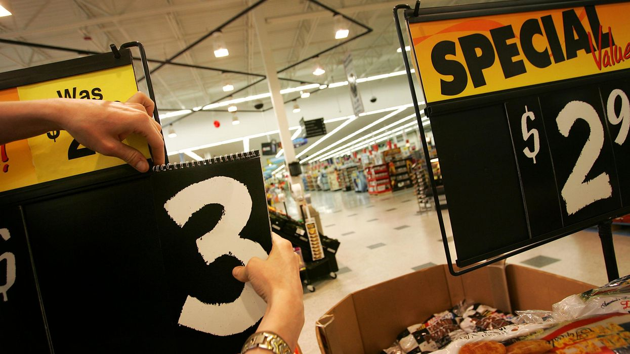 An employee changes a price placard in the grocery section of a Wal-Mart Supercenter.