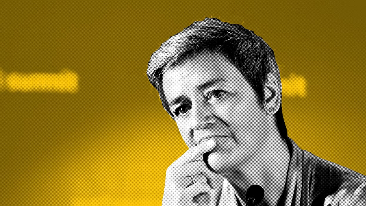 European Commission Executive Vice President Margrethe Vestager stares with her finger on her mouth in front of a microphone.