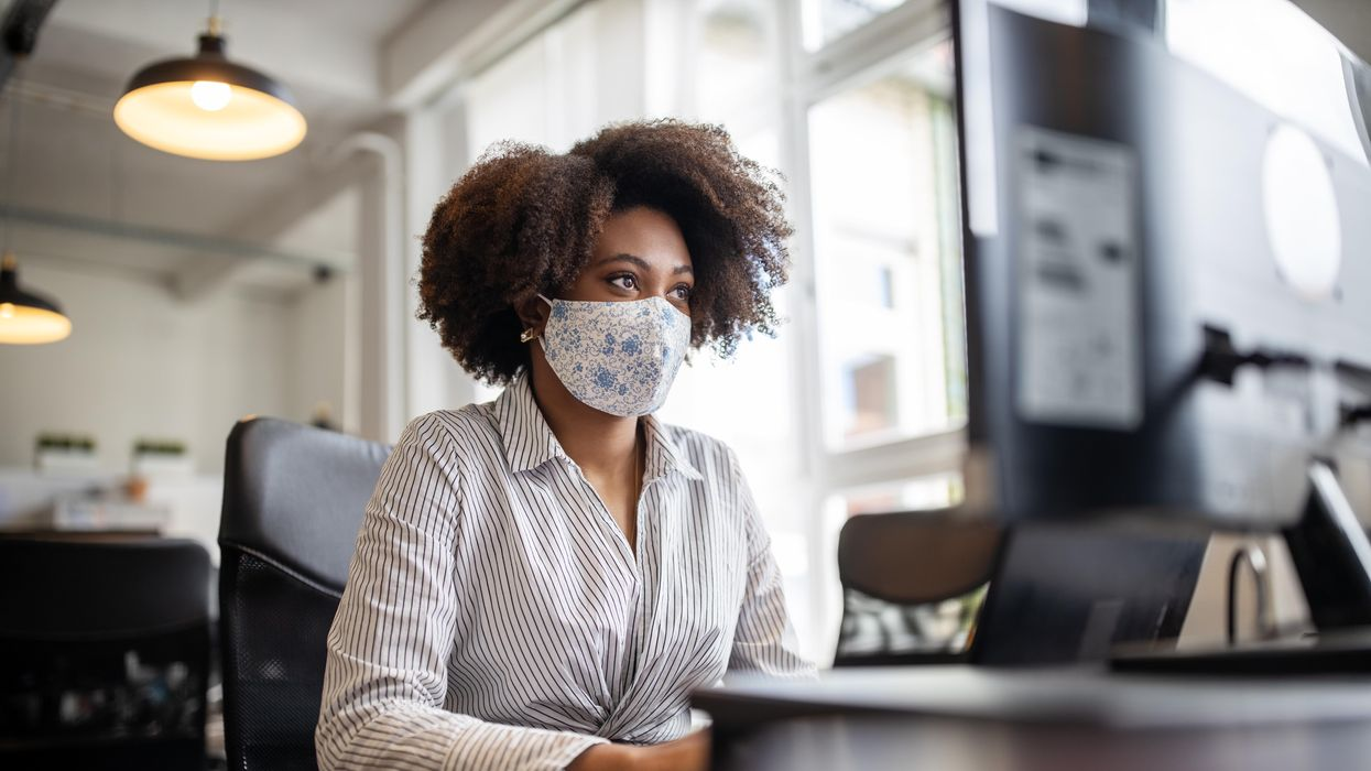Businessperson working at a desk with a mask on.
