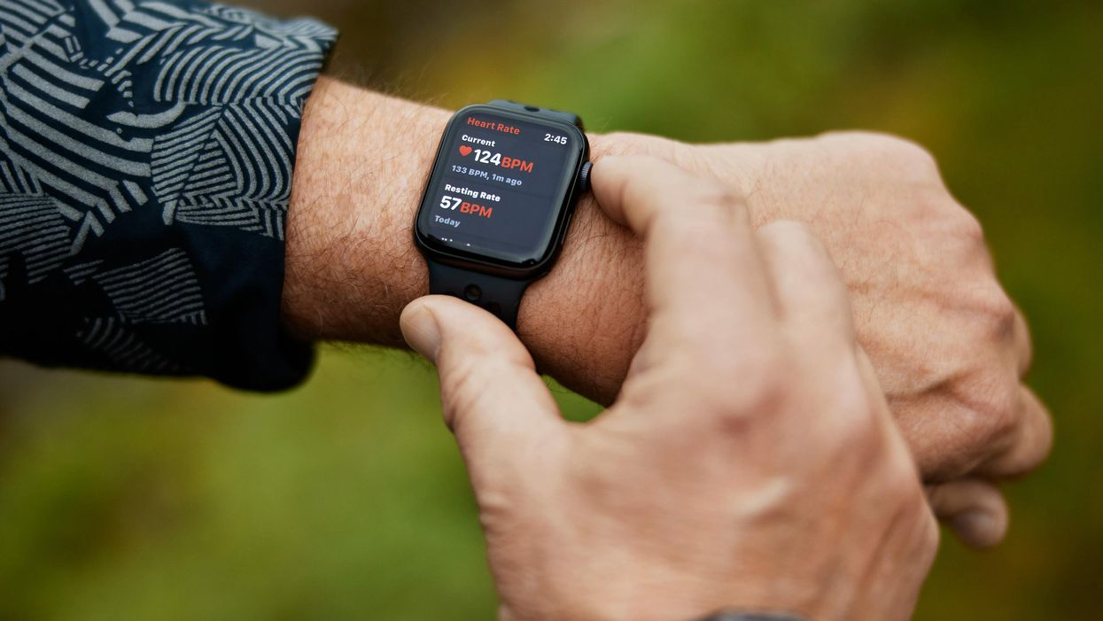 An Apple Watch on a person's wrist displaying a heart rate reading.