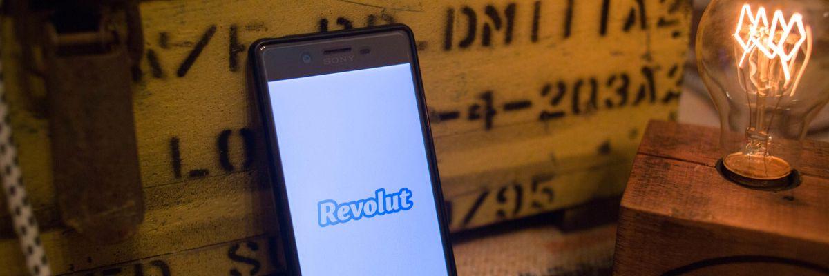 Revolut on a smartphone screen next to a lightbulb.