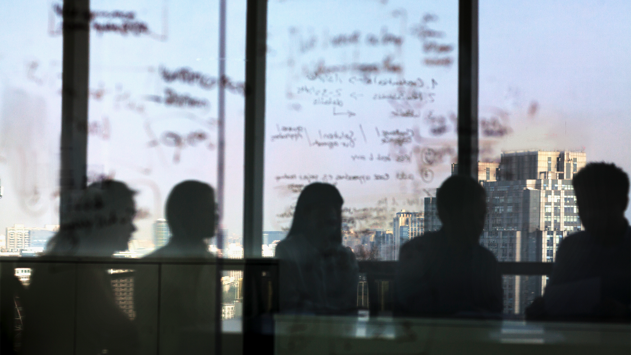 People in an office viewed through a window.