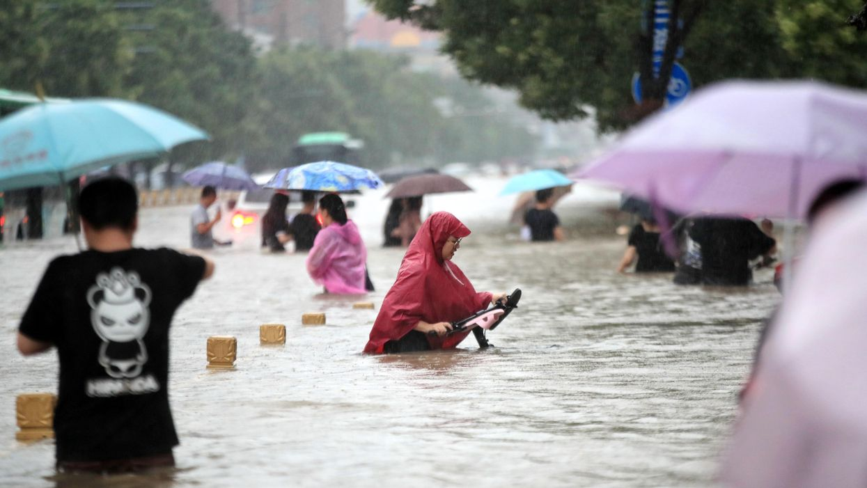 Chinese people walking through floodwaters