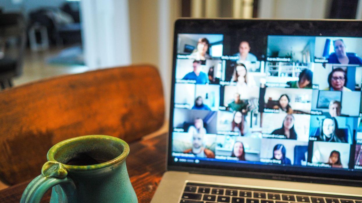 Coffee mug next to laptop showing video call grid.