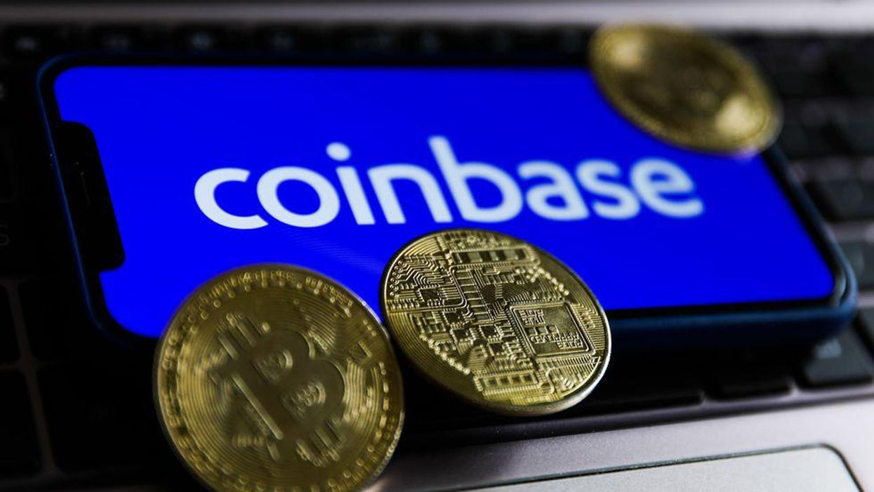 Coinbase logo displayed on a phone screen surrounded by Bitcoin