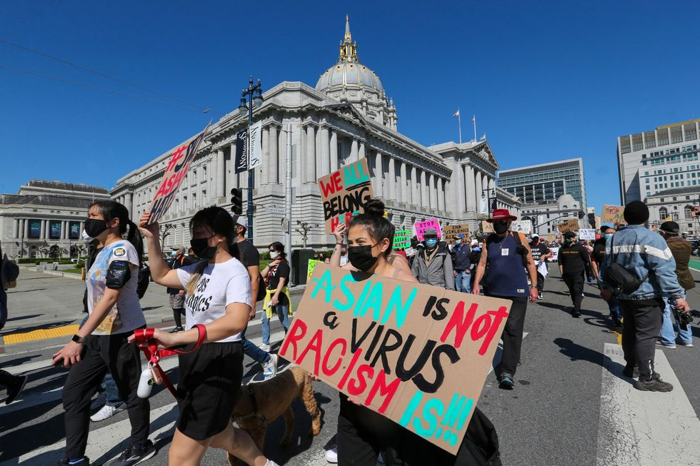 Demonstrators hold up signs as they take part in an anti-Asian American hate march and rally at  City Hall in San Francisco on Saturday, March 27. The march was organized by the Chinese Consolidated Benevolent Association.