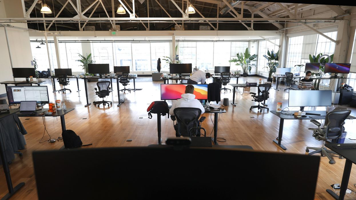 An office full of work stations with masked employees