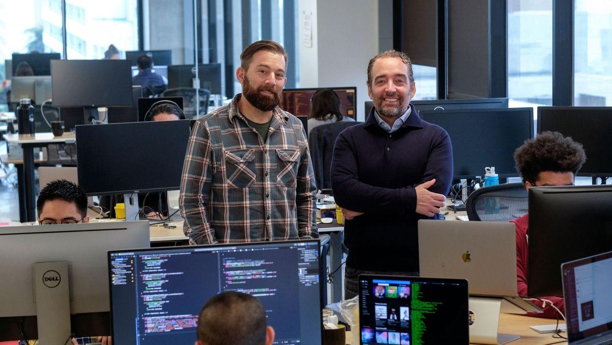 Doug Hirsch and Trevor Bezdek standing among employees