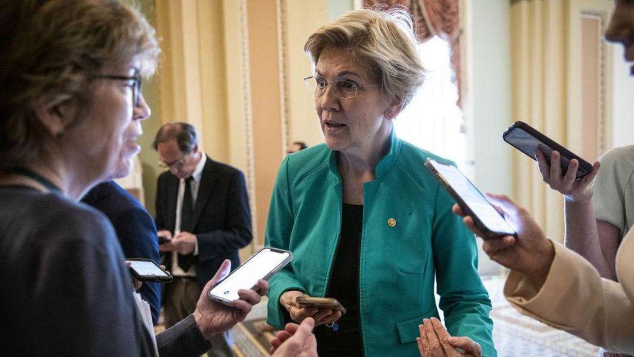 Senator Elizabeth Warren speaks as onlookers record her on their phones at the Capitol.