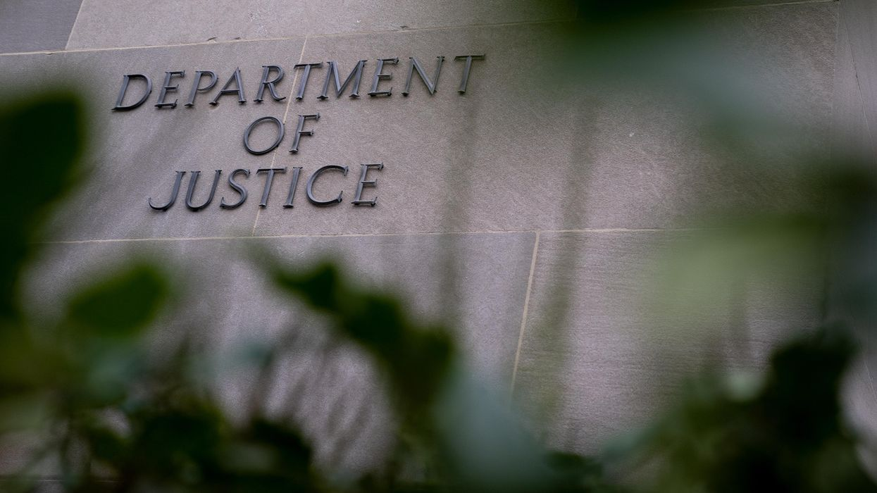 """Exterior photo of the """"Department of Justice"""" sign mounted on the outside of the building"""