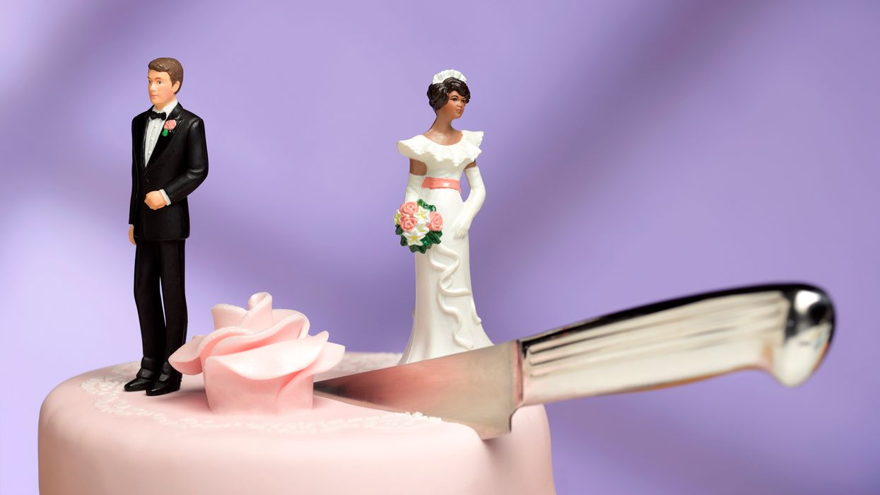 Figurines on top of a wedding cake with a knife in it