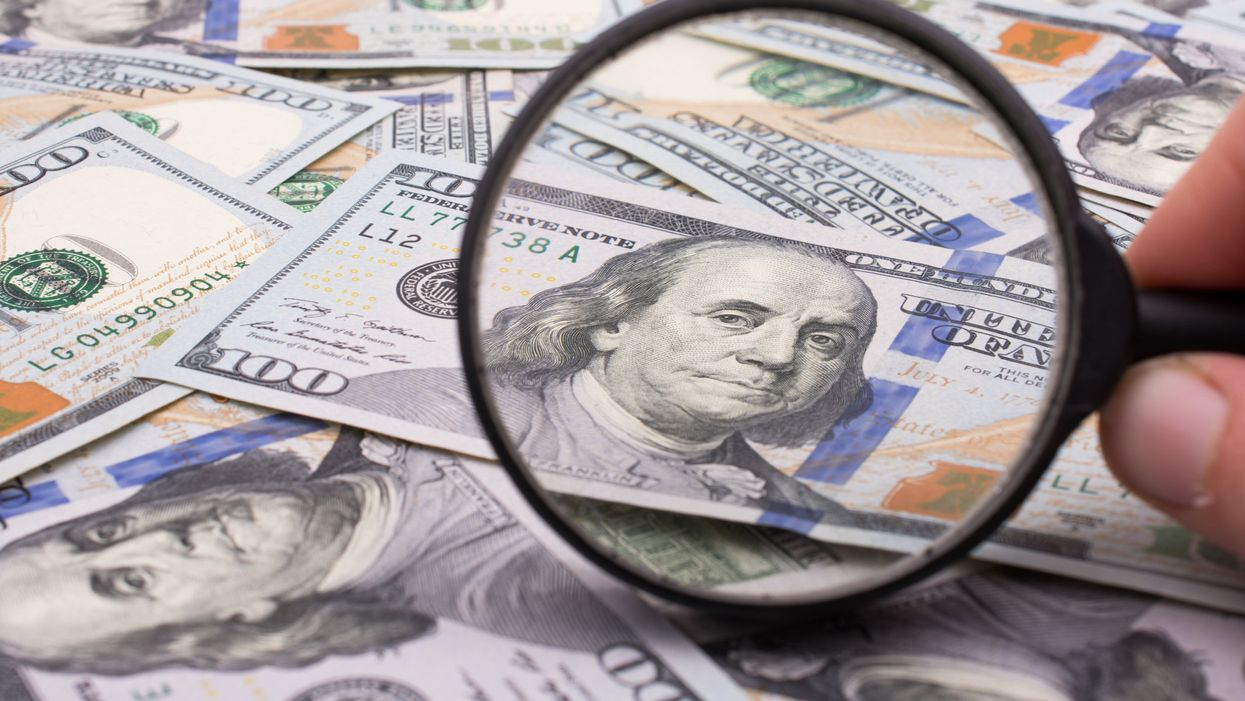A magnifying glass looking at a stack of $100 bills