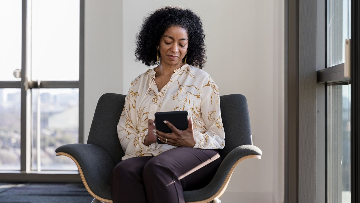 A woman sits in a chair looking at a tablet