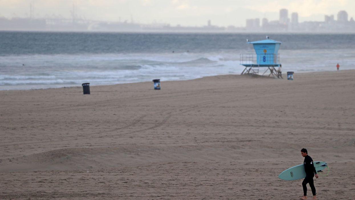 A surfers walks on a California beach
