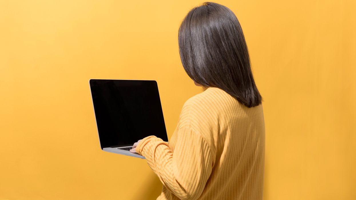 A woman looking at blank computer screen