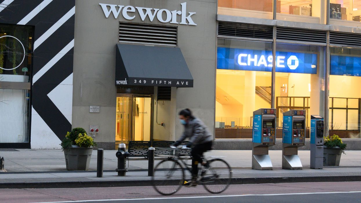 A person rides a bike past a WeWork office in Manhattan