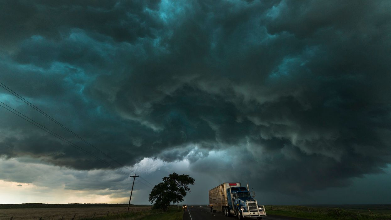 Big-rig truck driving under dark storm clouds