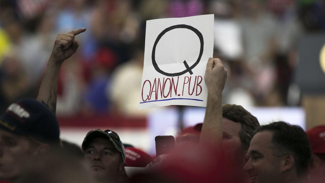 A person holding a QAnon sign