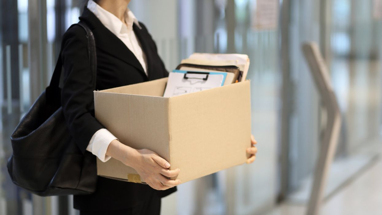 Woman leaving office with a box of her stuff
