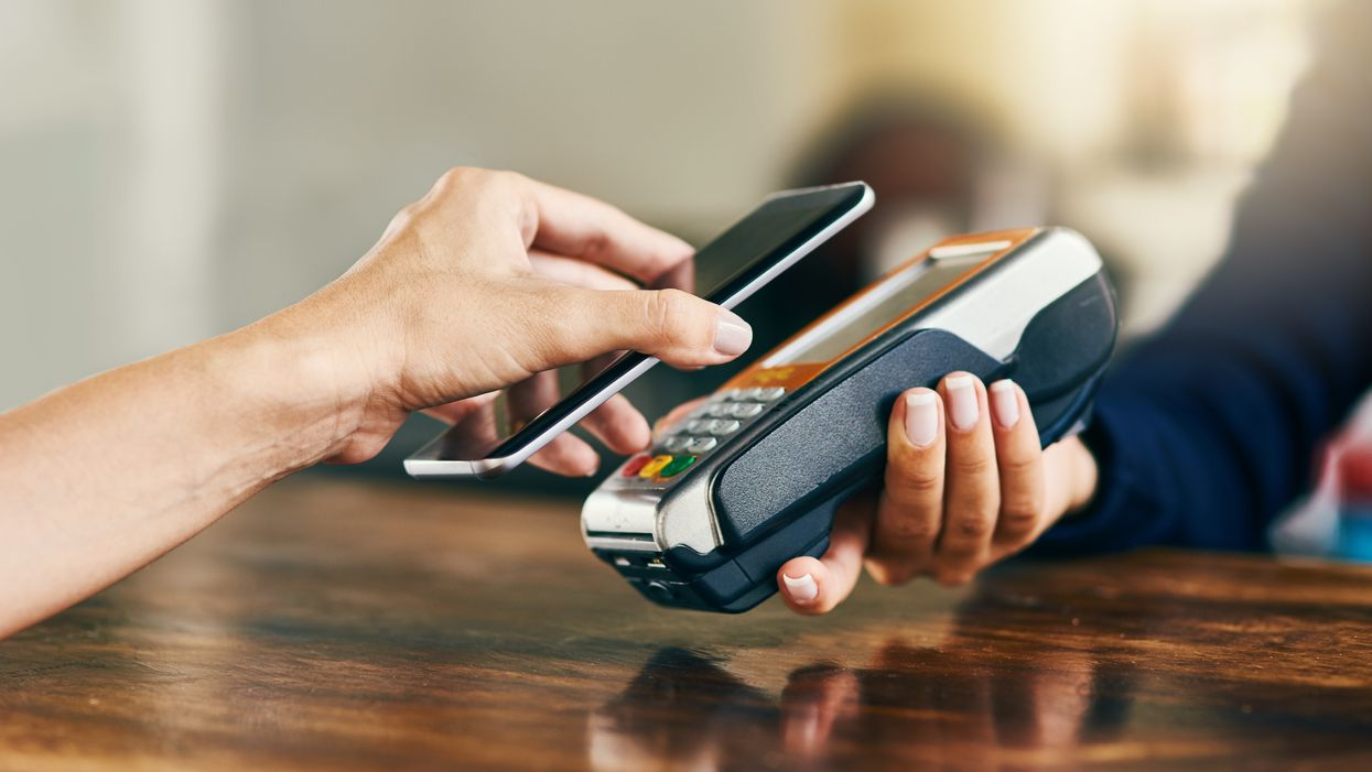 Closeup of an unrecognizable person using her phone to scan and pay a bill on a card machine at a cafe during the day.