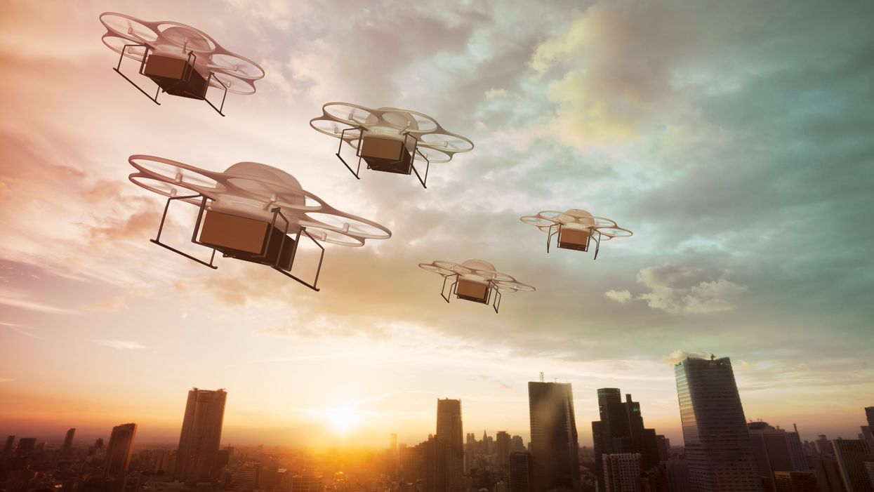 Five drones fly over a city