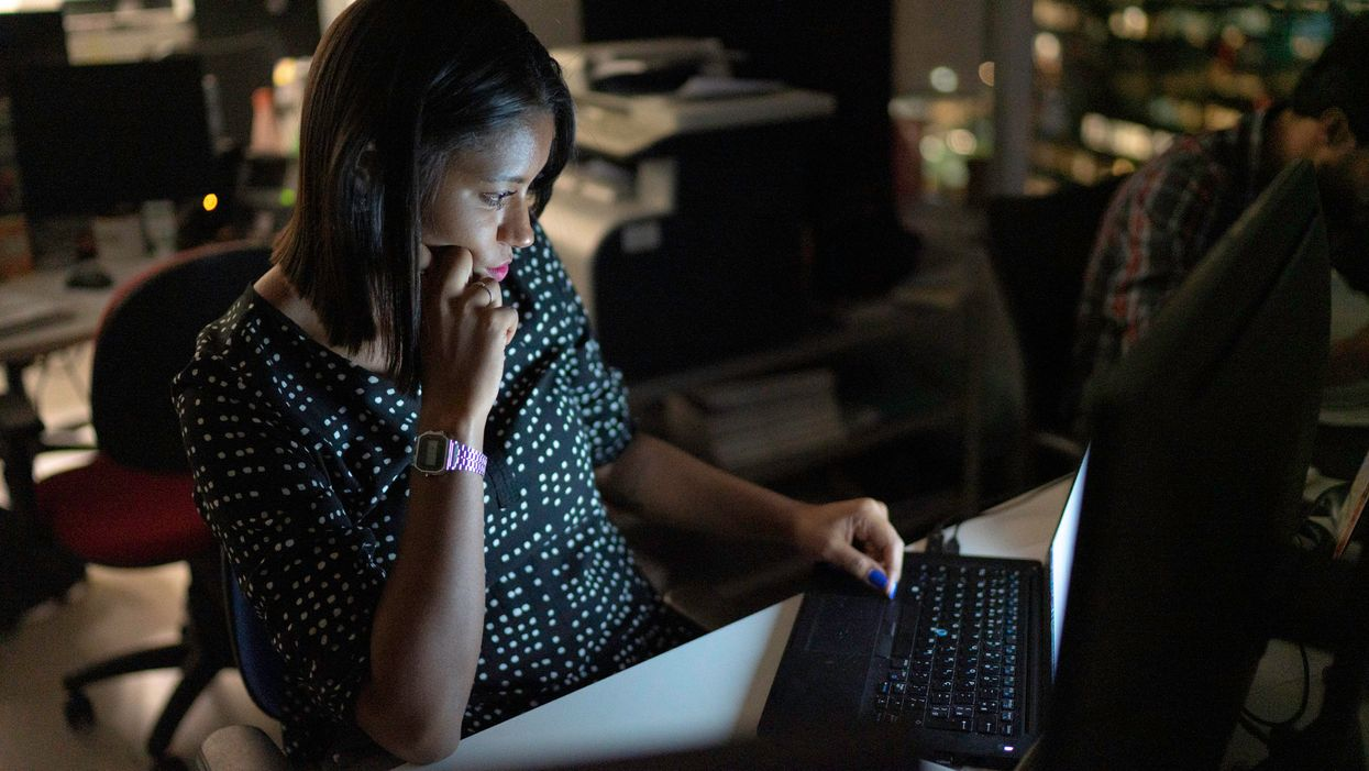 A disgruntled worker sitting at her computer in the dark