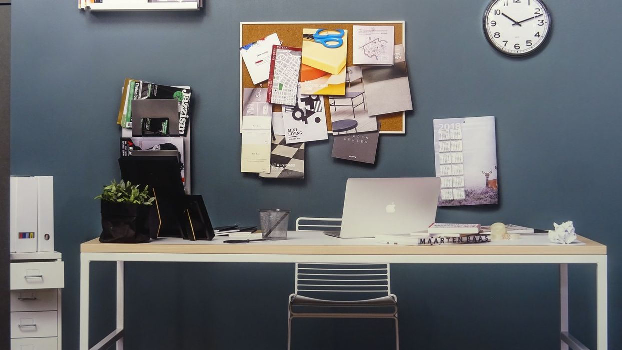 A desk with a bunch of office supplies on it