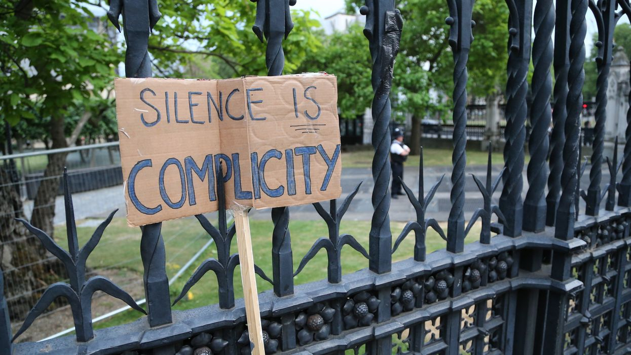"""A sign that says """"silence is complicity"""""""