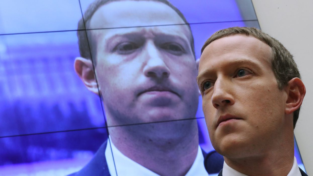 Mark Zuckerberg standing in front of his own face on a screen