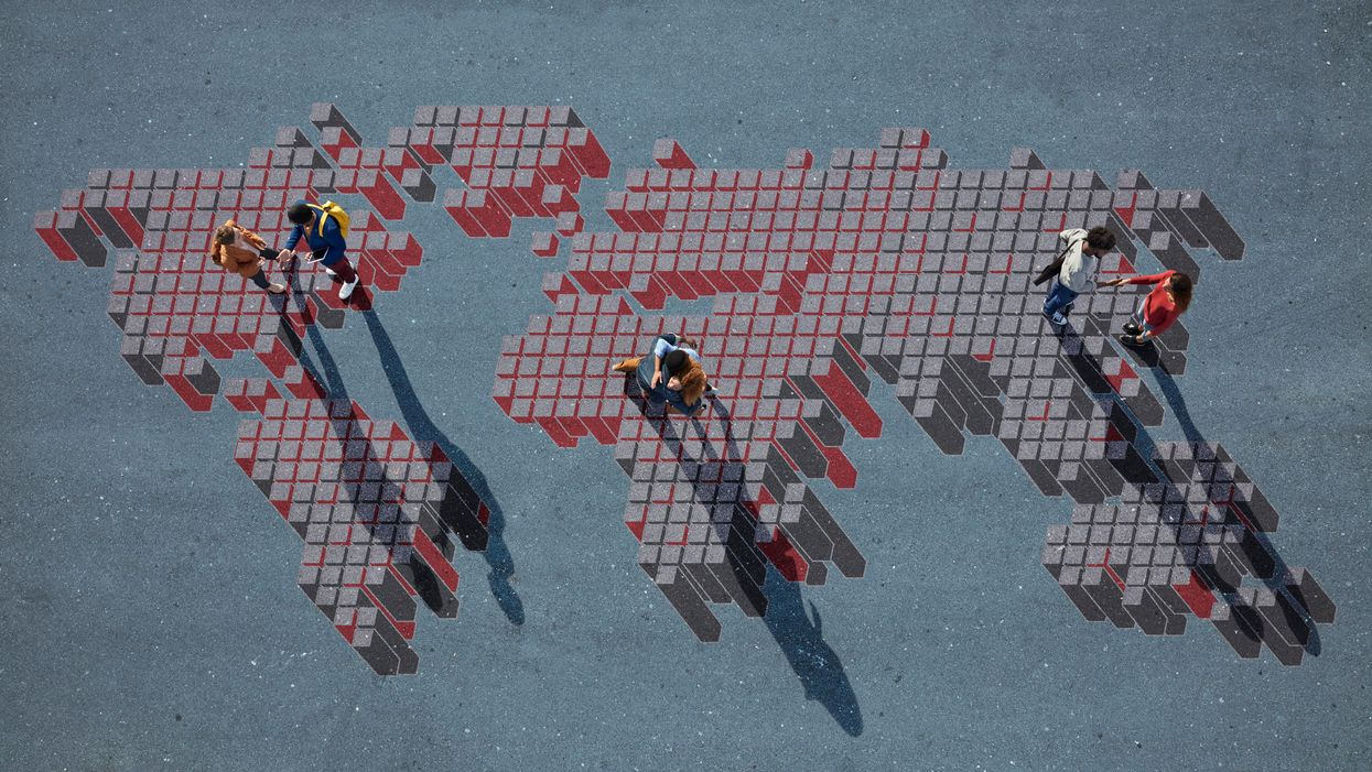 People standing and shaking hands on a pixelated drawing of a world map
