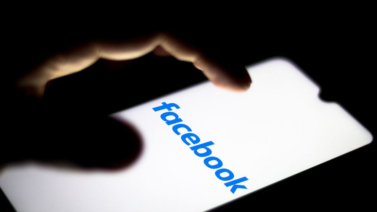 A finger touching a phone with the Facebook logo