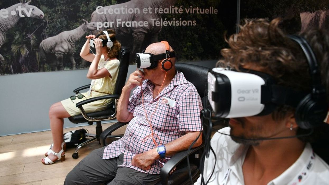 Three people use Samsung Gear VR headsets.