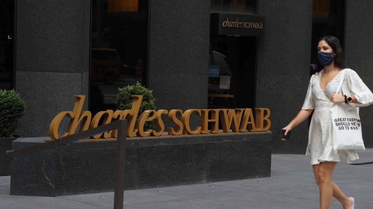 A woman walking by a Charles Schwab building