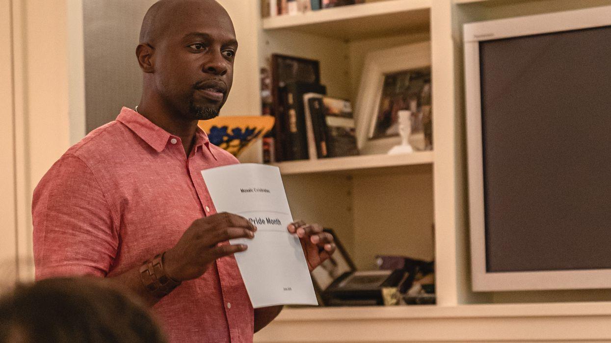 Michael Baptiste holding up paper for a presentation