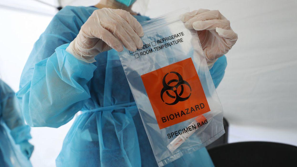 A doctor holding a specimen bag
